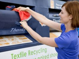 woman putting clothes in recycling bin